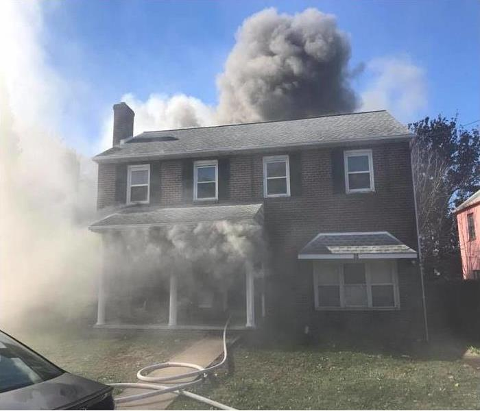 House fire with dark smoke coming out of windows and doors